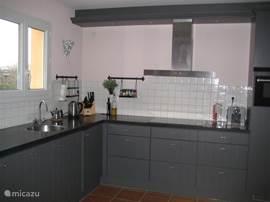 De ruime en moderne keuken voorzien van vaatwasser, extra grote koelkast, aparte vriezer en oven met combimagnetron.