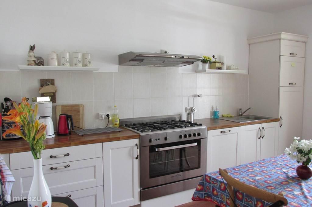 Ruime keuken met vaatwasser, groot fornuis, magnetron, voorraadkast en vriezer.