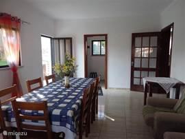 de leefruimte, met aan de zijkant een aparte ruimte met wasmachine en strijkplank, kastje met schoonmaakspullen, rechts de deur naar de keuken,