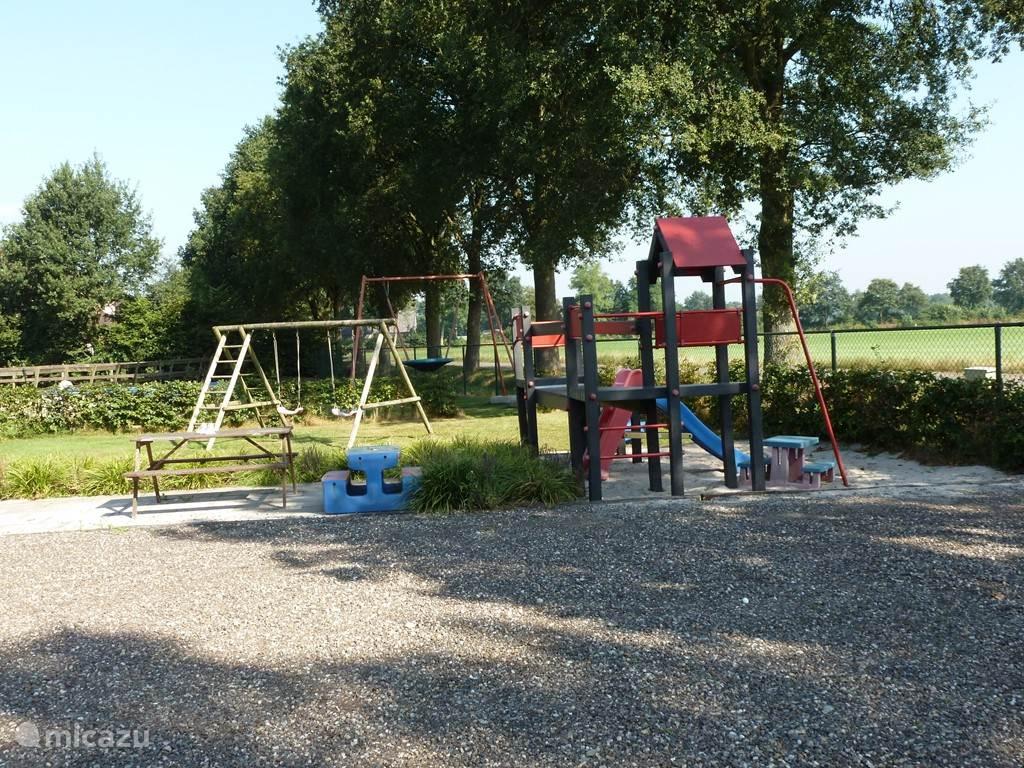 Speeltuintje met schommels, speelhuisje en een trampoline
