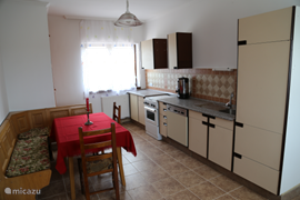 This is the kitchen in the cottage 'Kronos'. The dining area has space for four or five people. The kitchen includes a stove dishwasher and refrigerator. There is also a coffee maker.