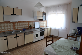 This is the kitchen of the cottage Sirius. In the kitchen you will find a coffee maker, refrigerator dishwasher and gas stove. There is also a large pantry. The table can accommodate four people.