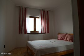The bedroom in the house 'Orion' with double bed. On the left is a linen closet (off screen). On the bed coverlet with the traditional Hungarian embroidery. Lies