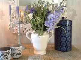 Eettafel met spiegel in de woonkamer. Bloemen zijn altijd aanwezig en staan overal in de woning