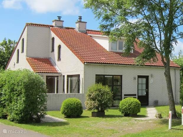 Het aanzicht van de bungalow met zonnig terras en 2 parkeerplaatsen op eigen terrein