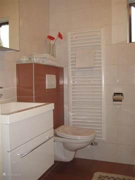 Badkamer begane grond, met douche, toilet, wastafel en ligbad.