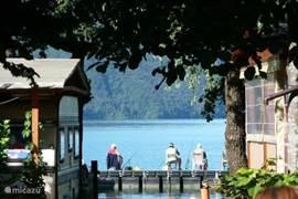 Uitzicht op het meer van Lugano. Waar vele watersporten beoefend kan worden. Zoals: zeilen, surfen, zwemmen, varen, en dobberen op een luchtbed.