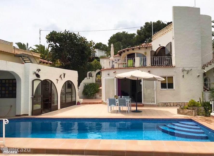 De hoofdwoning met onder het appartement, gezien vanaf het zwembad met links de gezellige zomerkeuken.