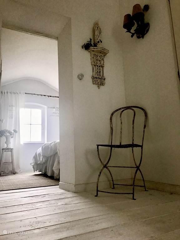 Via de houten trap met kroonluchter komt U op de bovenetage