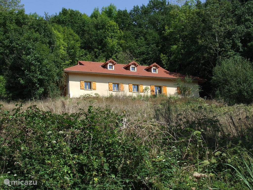 Vooraanzicht van het hoog op de heuvel staande vakantiehuis. Het linker gedeelte van dit huis wordt verhuurd, het rechter gedeelte wordt enkele weken per jaar bewoond door de eigenaar.