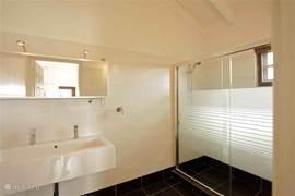Tweede badkamer op de eerste verdieping voor de twee andere slaapkamers. Deze ook lichte badkamer biedt warme douche, wastafel en toilet.