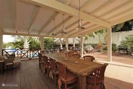 De porch is volledig overdekt en kijkt uit op het zwembad en de Curaçaose heuvels. De grote eettafel is dan ook ondergebracht op deze prachtige ruime porch.