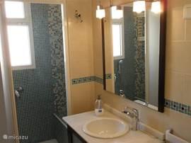 Badkamer met wastafelmeubel, toilet, bidet en douche.