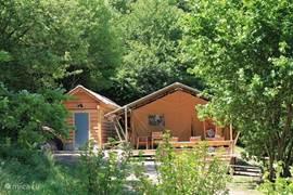 Het badgebouw, met buitenverlichting, staat vlak naast de tent; de tent zelf staat op een open plek in het bos.