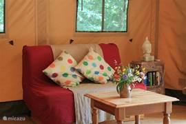 Het woongedeelte met tweepersoons slaapbank, kasten, eettafel en 6 stoelen en een laag tafeltje.