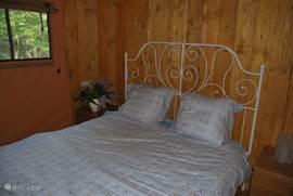 De eerste slaapkamer, met een romantisch tweepersoonsbed, nachtkastjes en hangruimte.