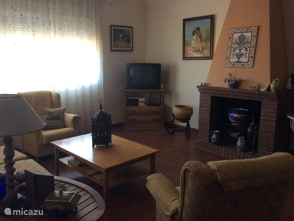 Dit is de woonkamer hier staan 2 fauteuils en een 3 sits bank. Verder is er een eethoek aanwezig met 4 stoelen.