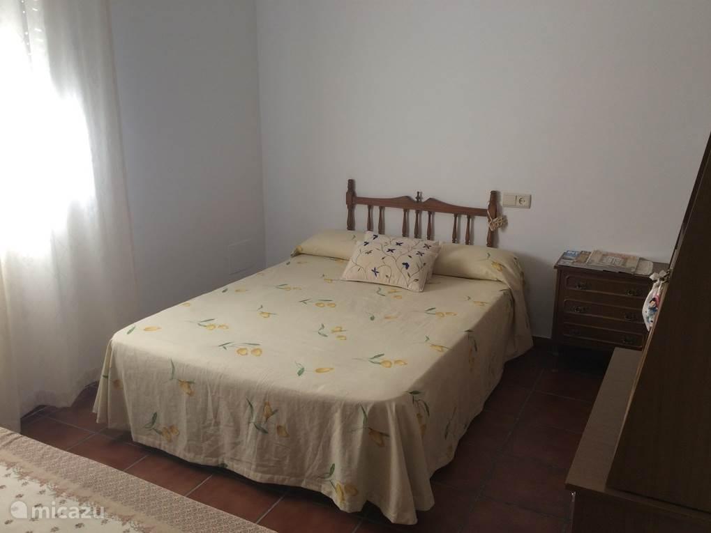 Dit is een slaapkamer met een tweepersoonsbed en een eenpersoonsbed, deze kamer heeft een inbouwkast en een grote gaderobekast.