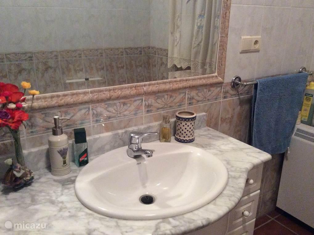 Hier ziet u de wastafel. In de badkamer is ook een elektrische kachel aanwezig.