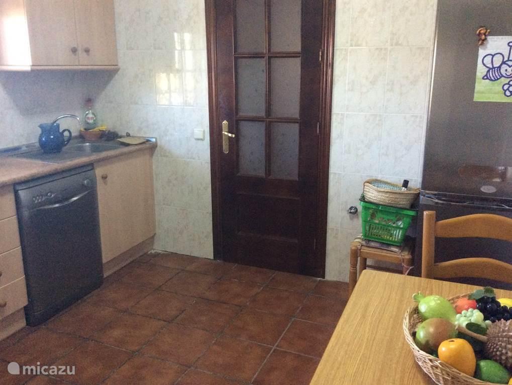 In de keuken is een tafel aanwezig met 2 stoelen. Via de keuken is er een deur met een trap naar beneden, via deze trap kom je in de garage onder het huis.