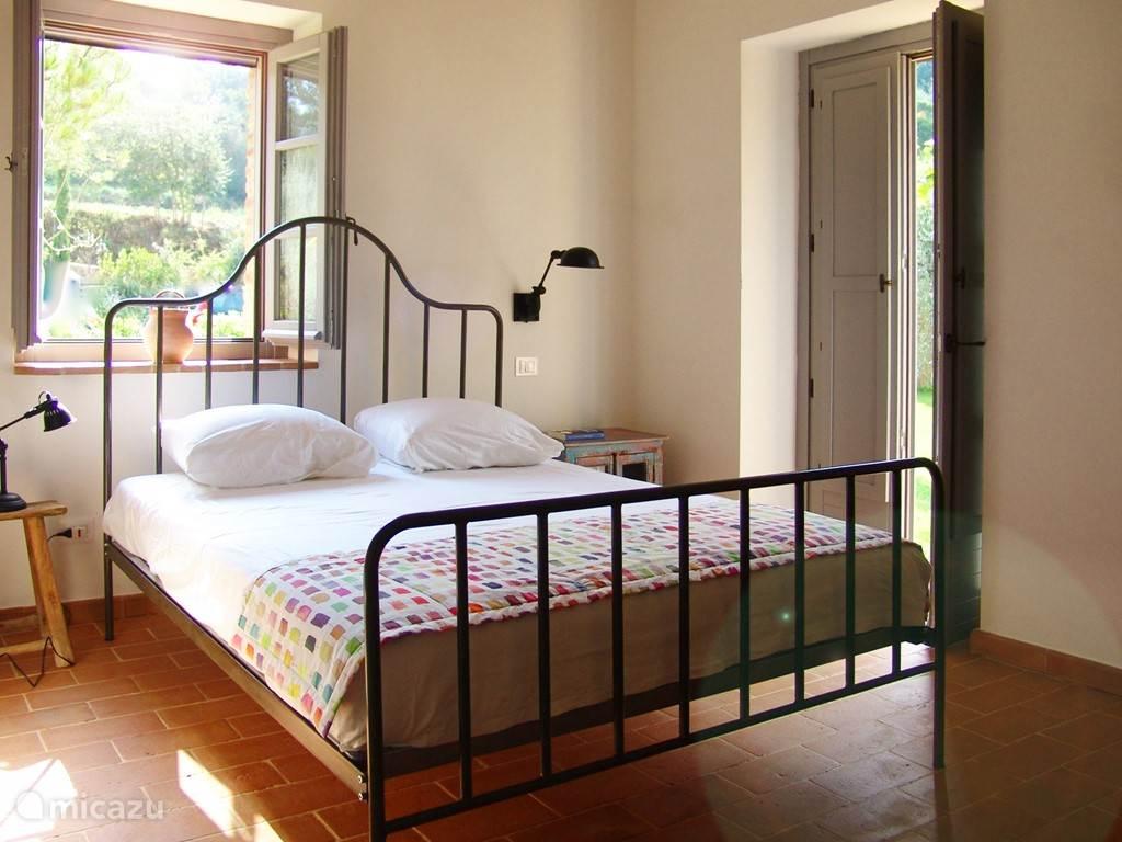 De masterbedroom met openslaande deuren naar de tuin en terras. Direct aangrenzend de badruimte.