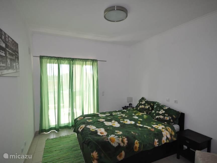 Slaapkamer met 1 persoons bed en toegang tot terras
