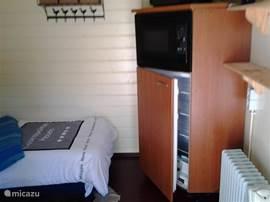 Een extra koelkast en magnetron in de blokhut. Daarboven staat ook nog een tv, dus beide slaapkamers beschikken over een tv.