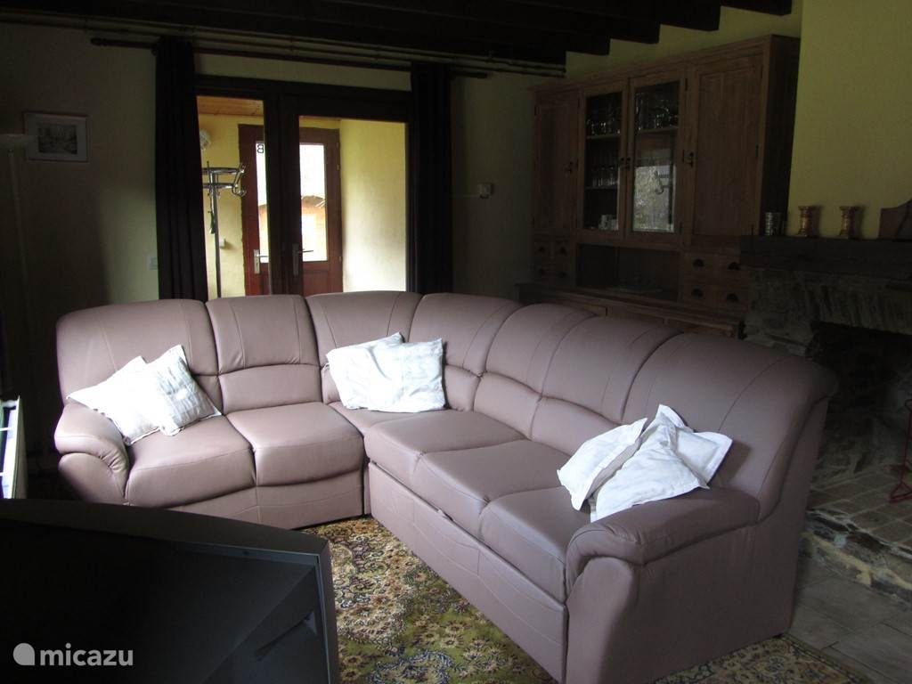Woonkamer met salon, tafel, 6 stoelen en kitchenette