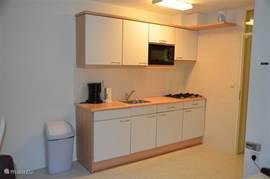 Goede keuken voorzien van koelkast, gasfornuis en magnetron