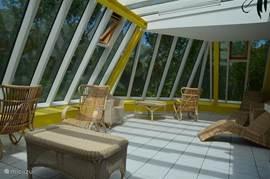In de gemeenschappelijke wintertuin op de tweede verdieping kunt u ook in het zonnetje zitten bij koud weer.
