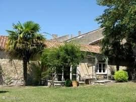 Zicht op de tuin façade van de gite en het terras vanaf de volledig ommuurde tuin de ideale plek om te onthaasten.
