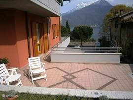 Ruim terras met tafel, stoelen en twee ligstoelen, parasol, barbecue, en aparte opgang van de straat met gesloten hek.