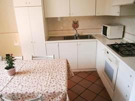 Ruime en lichte keuken met magnetron, oven, vriezer, koffiezetter, strijkplank en strijkijzer.