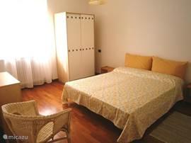 ruime lichte slaapkamer met kledingkast, ladenkast en rieten feauteuil. Er is plaats voor een extra bed of kinderledikant.