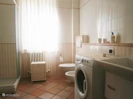 Ruime badkamer met douche, ligbad en wasmachine