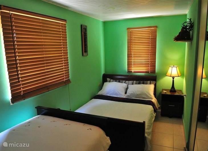 Slaapkamer met dubbel bed en extra bed waar onder uitschuifbaar bed nacht kastje met lampje