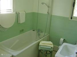 One of the two bathrooms with a tub and shower combination and a screen, and a sink The bathroom is 6 m²