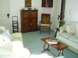 The living room is very cozy. There is a 3 seater sofa, armchair and other chairs, a coffee table. The dining room is a separate room with table and chairs, and a buffet lamp.