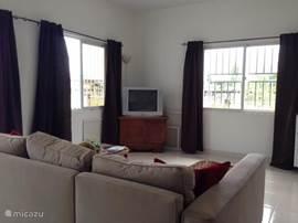 Woonkamer met hoekzitbank voor 4-5 personen met televisie en salontafel.