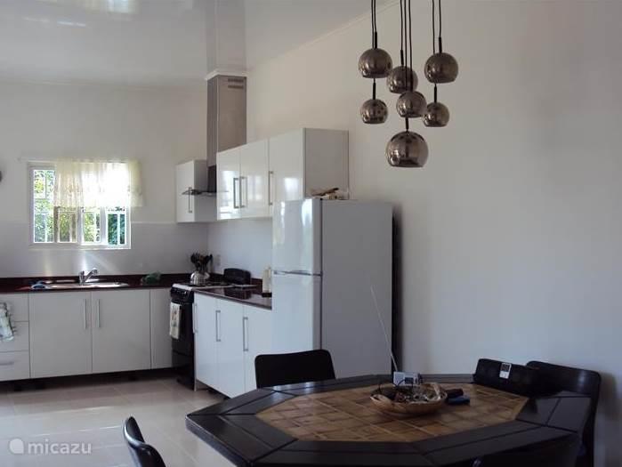 Een open keuken met aaneengesloten eethoek.