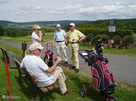 Afternoon of golf with friends on the 18th hole slightly hilly and golf course.