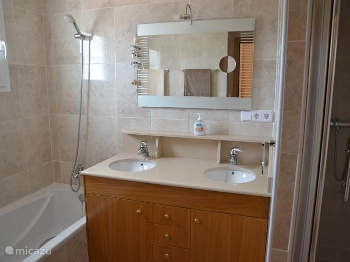 Deze badkamer met ligbad en aparte douchecabine en dubbele wastafel plus gescheiden toilet is gelegen op de bovenste verdieping en is toegankelijk vanuit de masterbedroom .