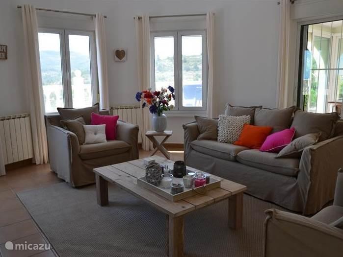 De woonkamer, ruim van opzet in ibiza stijl, heeft een zitgedeelte met sateliet TV en radio plus DVD speler en is gezellig ingericht. De kamer is voorzien van airco zowel koud als warm. Het geheel heeft een plavuizen vloer , en rondom rolluiken.