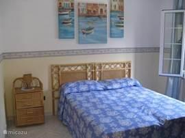 Een tweepersoons slaapkamer met openslaande deuren naar het balkon