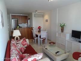 Gezellige huiskamer met 4 persoons eethoek en zithoek, airco, elektrisch bedienbare rolluiken, marmeren vloeren in het hele appartement.