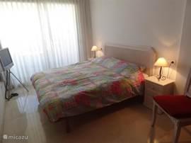 Romantische zeer ruime slaapkamer met TV en airco en direct toegang tot het riante terras middels schuifpui.Bed 200x180 cm