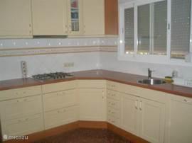 ruime keuken met 4 pits gasstel, vaatwasser, grote koelkast, wasmachine en oven