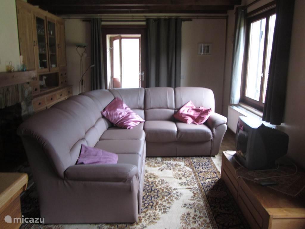 Woonkamer met salon, tafel, 6 stoelen en kichenette
