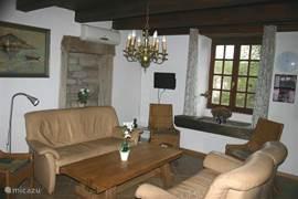 De woonkamer met een twee en een driezits en 4 stoelen er is ook splitairco die op kille dagen warmte kan geven
