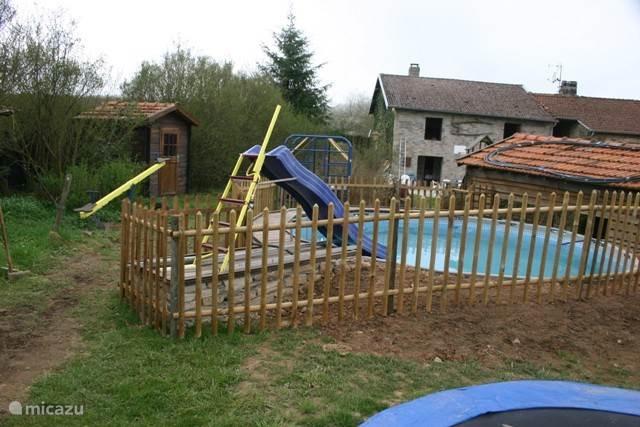Het zwembad met op de achtergrond net voor de blokhut de wip.